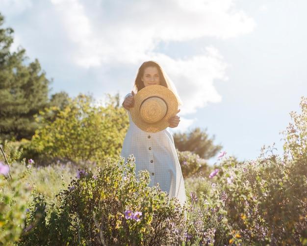 Vista frontal da mulher na natureza posando enquanto segura o chapéu