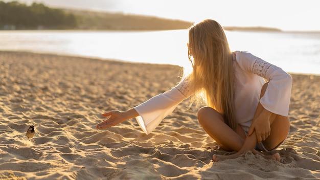 Vista frontal da mulher na praia com pássaro