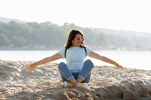 Vista frontal da mulher na praia, desfrutando de areia