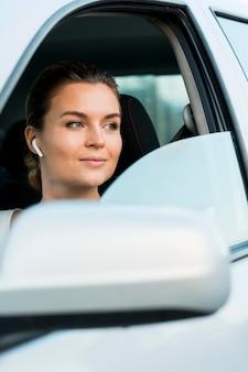 Vista frontal da mulher no carro pessoal