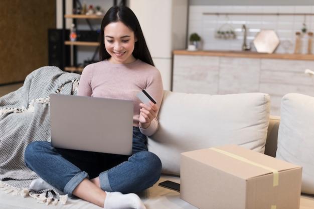 Vista frontal da mulher no sofá, segurando o laptop e cartão de crédito