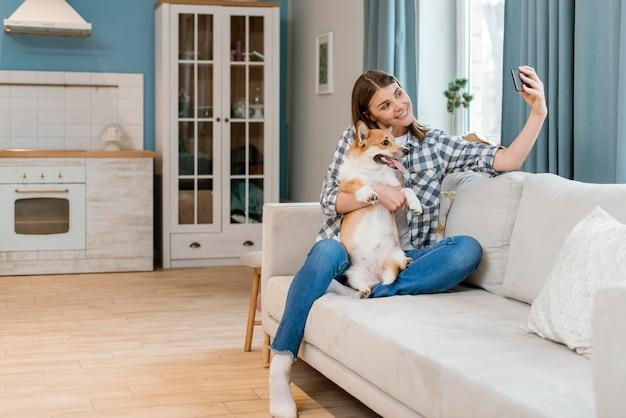 Vista frontal da mulher no sofá tomando selfie com seu cachorro