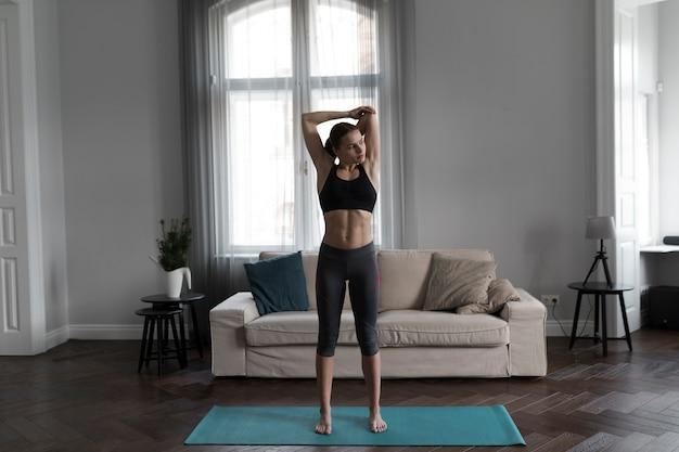 Vista frontal da mulher no sportswear, estendendo-se no tapete de ioga