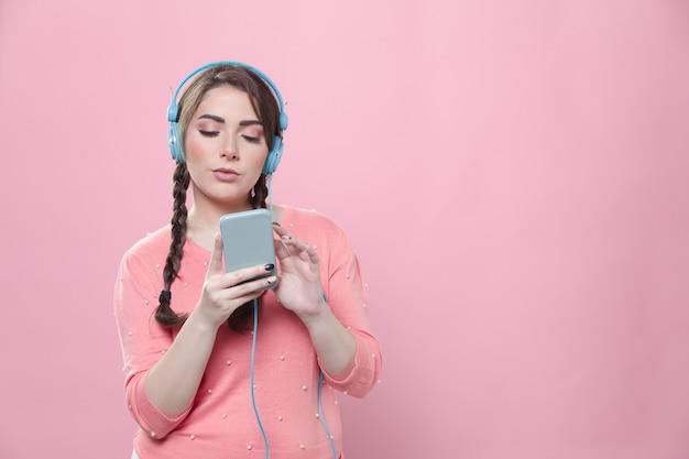 Vista frontal da mulher ouvindo música em fones de ouvido enquanto segura o smartphone