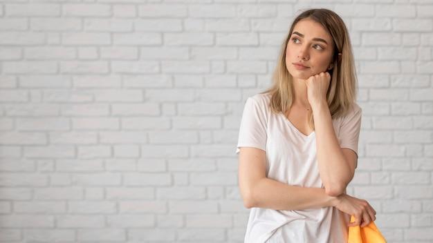 Vista frontal da mulher pensativa, segurando o pano com espaço de cópia