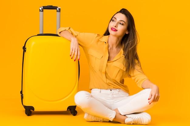 Vista frontal da mulher posando alegremente ao lado de sua bagagem