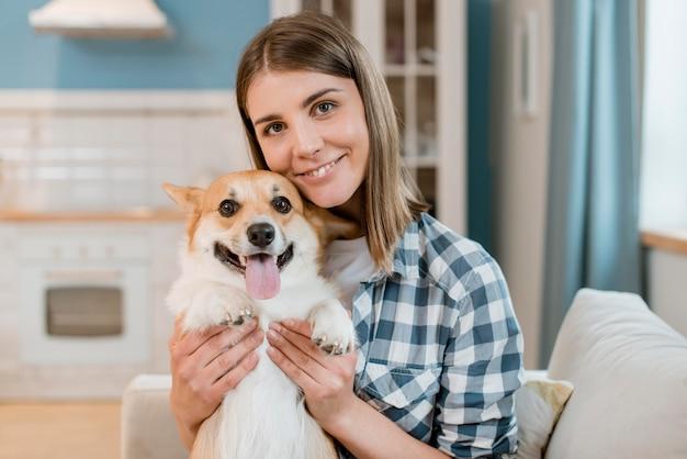 Vista frontal da mulher posando alegremente com seu cachorro