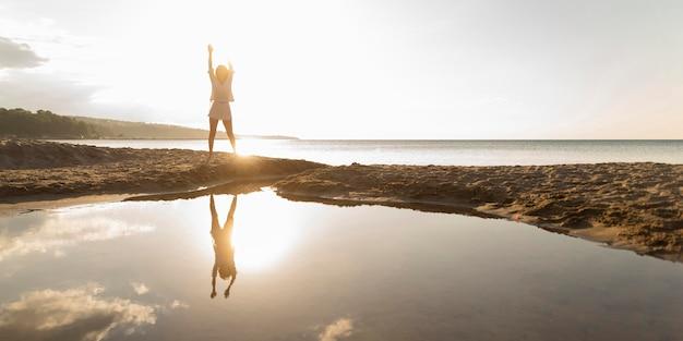 Vista frontal da mulher posando ao ar livre com água