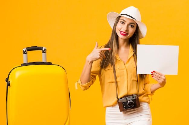 Vista frontal da mulher posando ao lado de bagagem enquanto apontando para o papel em branco