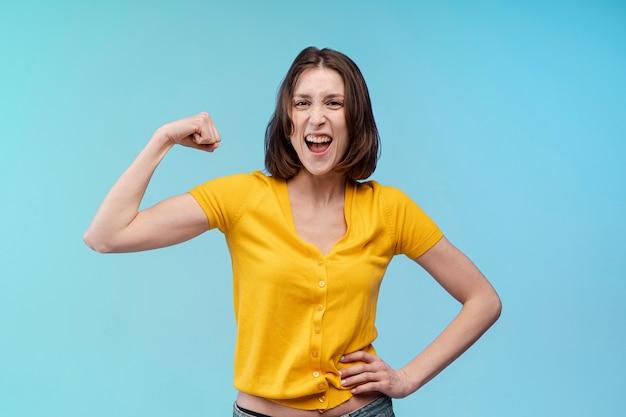 Vista frontal da mulher posando ao mostrar seu bíceps