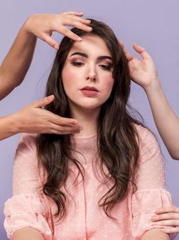 Vista frontal da mulher posando as mãos de outras mulheres em volta da cabeça