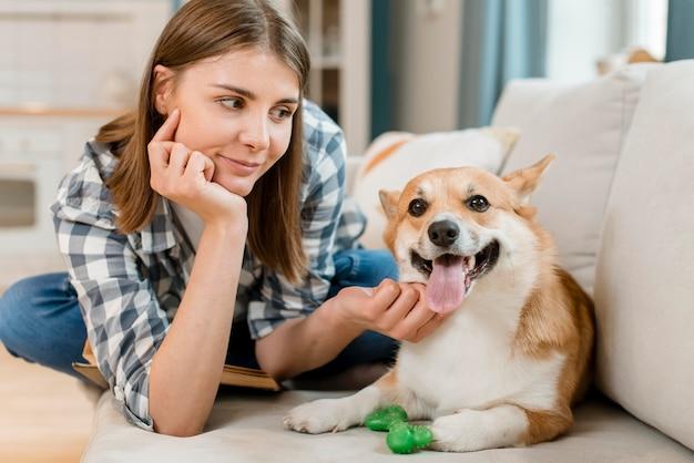Vista frontal da mulher posando com cachorro no sofá