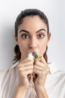 Vista frontal da mulher posando com diamante cobrindo a boca