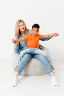 Vista frontal da mulher posando com menino sorridente