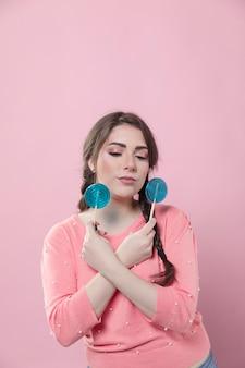 Vista frontal da mulher posando com pirulitos e cópia espaço