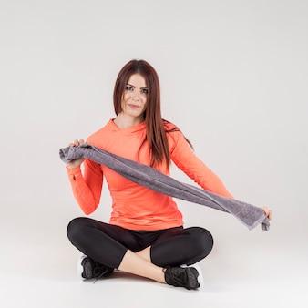 Vista frontal da mulher posando em trajes de ginástica, segurando a toalha
