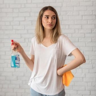 Vista frontal da mulher posando enquanto segura a solução e pano de limpeza