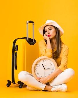Vista frontal da mulher posando enquanto segura o relógio ao lado de bagagem