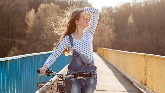 Vista frontal da mulher posando na ponte com bicicleta