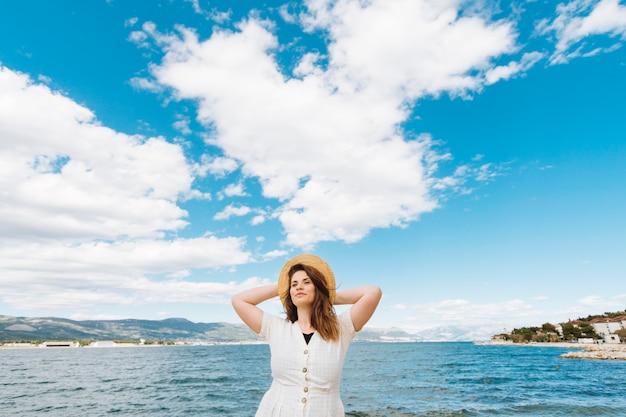 Vista frontal da mulher posando no oceano com nuvens no céu
