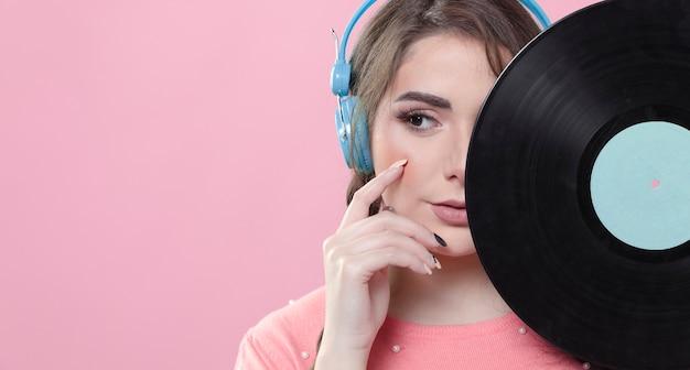 Vista frontal da mulher posando sedutoramente enquanto cobre metade do seu rosto disco de vinil