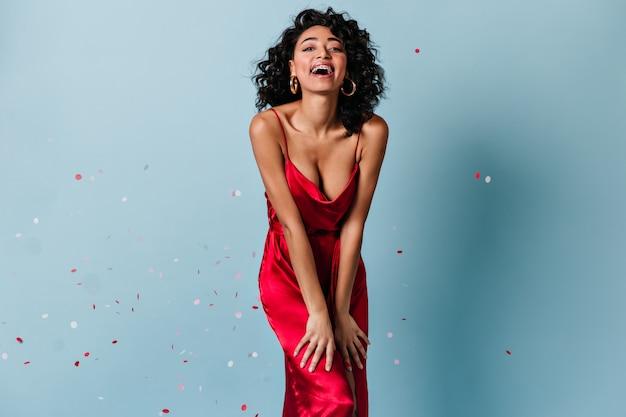 Vista frontal da mulher positiva rindo sob confete