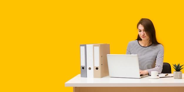 Vista frontal da mulher profissional trabalhando na mesa dela