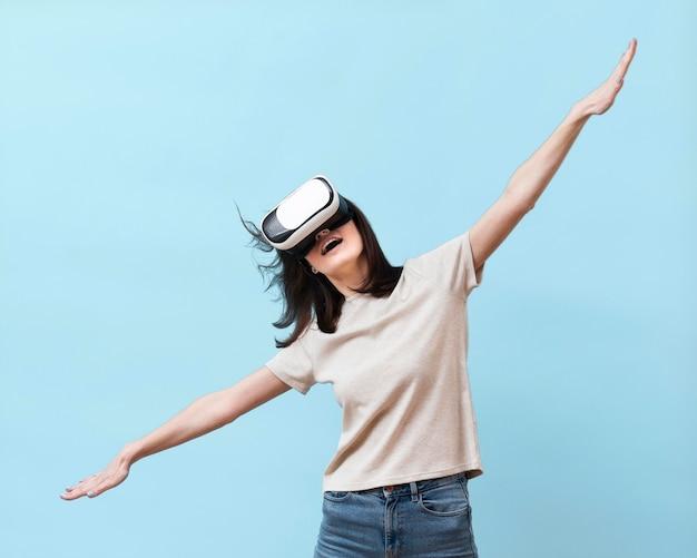 Vista frontal da mulher se divertindo com fone de ouvido de realidade virtual