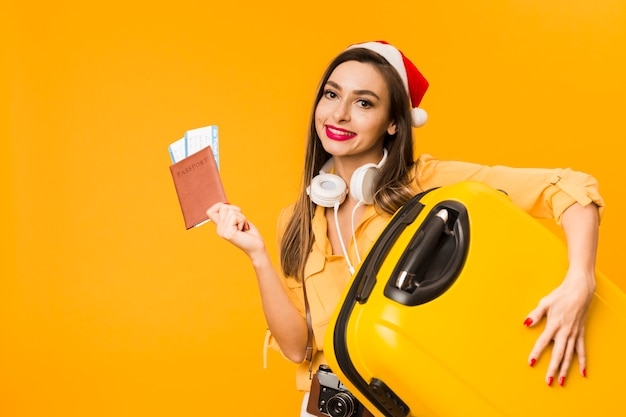 Vista frontal da mulher segurando a bagagem e passaporte com passagens de avião