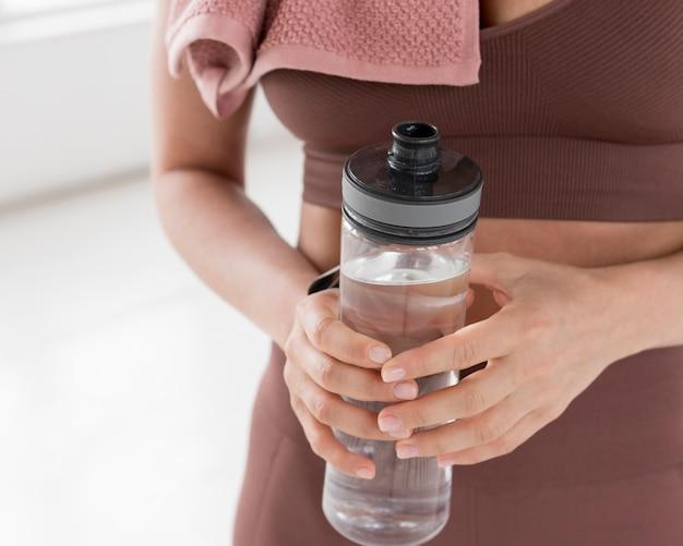Vista frontal da mulher segurando a garrafa de água