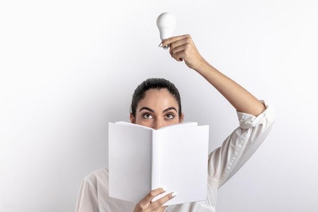 Vista frontal da mulher segurando a lâmpada e livro
