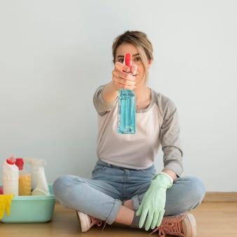 Vista frontal da mulher segurando a solução de limpeza