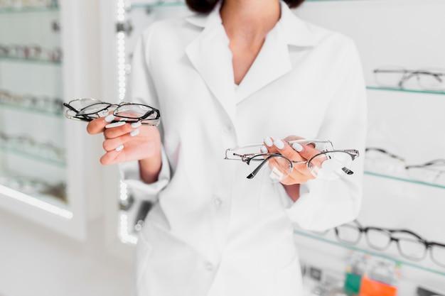 Vista frontal da mulher segurando armações de óculos