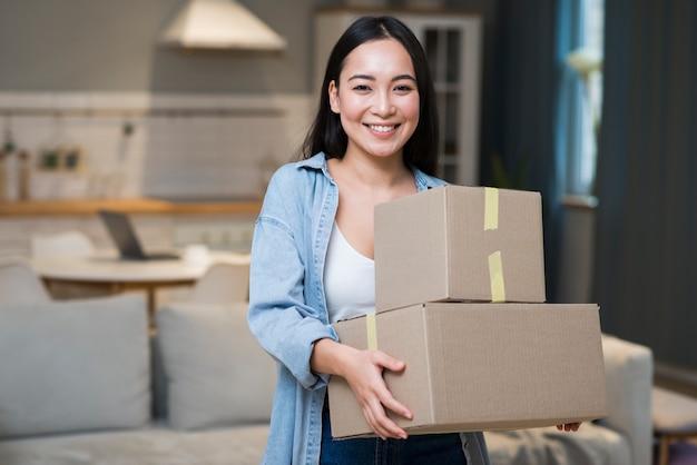 Vista frontal da mulher segurando caixas que ela pediu on-line