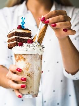 Vista frontal da mulher segurando delicioso milkshake