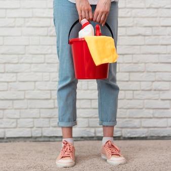 Vista frontal da mulher segurando o balde com material de limpeza