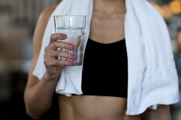 Vista frontal da mulher segurando o copo de água