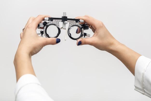 Vista frontal da mulher segurando o equipamento óptico