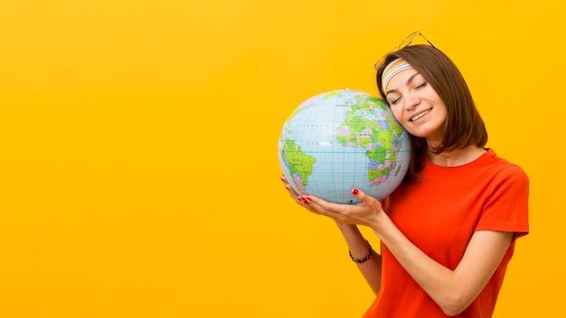 Vista frontal da mulher segurando o globo com espaço de cópia