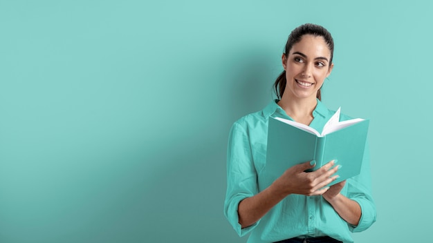 Vista frontal da mulher segurando o livro com espaço de cópia