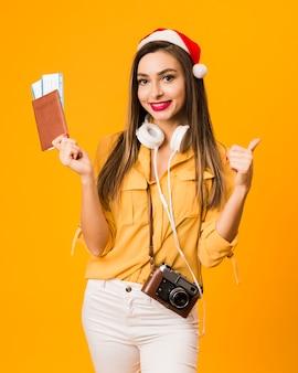 Vista frontal da mulher segurando o passaporte com bilhetes de avião e dando polegares para cima