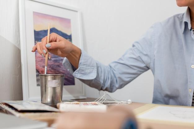 Vista frontal da mulher segurando o pincel