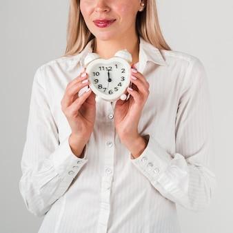 Vista frontal da mulher segurando o relógio