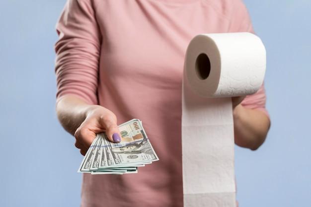 Vista frontal da mulher segurando o rolo de papel higiênico e oferecendo dinheiro