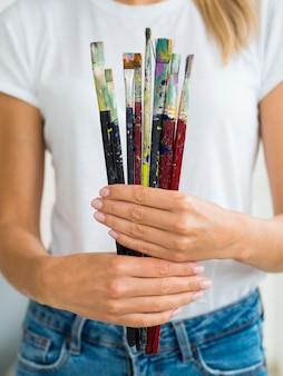Vista frontal da mulher segurando pincéis nas mãos