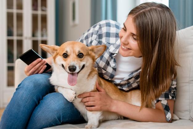 Vista frontal da mulher segurando smartphone e cachorro