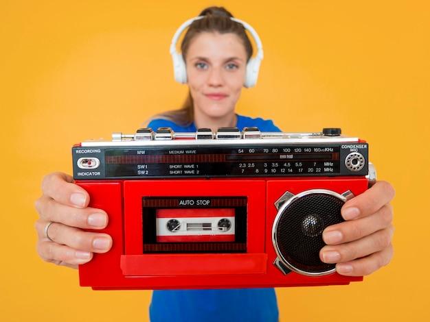 Vista frontal da mulher segurando um rádio