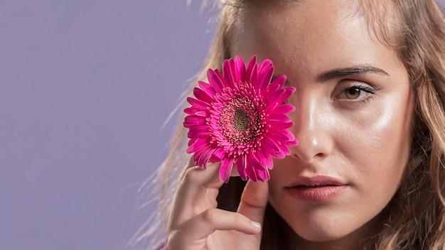 Vista frontal da mulher segurando uma flor perto do rosto com espaço de cópia