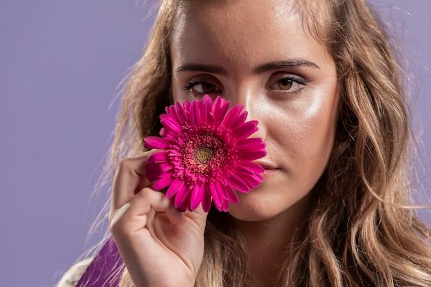 Vista frontal da mulher segurando uma flor perto do rosto