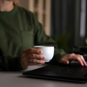 Vista frontal da mulher segurando uma xícara de café